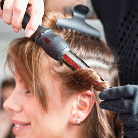curling: Hair salon - styling hair with curling tongs Stock Photo