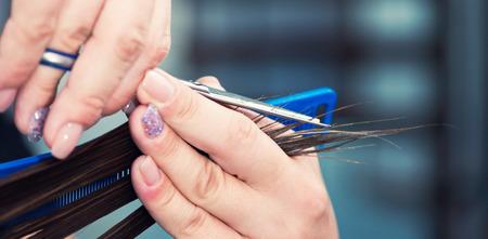 hairdresser cutting hair: Hairdresser cutting hair at hair salon. Close-up, convenient copy space