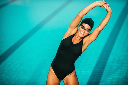 Female swimmer streching on poolside Stock Photo