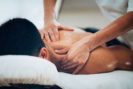 Physical therapist doing massage of males shoulder Stock Photo