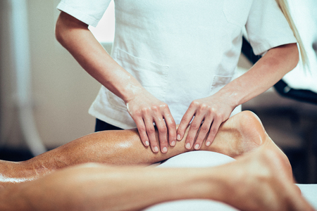 Masaje deportivo - Masaje terapeuta que trabaja con el paciente, masajear las pantorrillas. la imagen en tonos.
