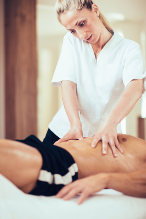 hands massage: Physical therapyst massaging sportsman stomach Stock Photo