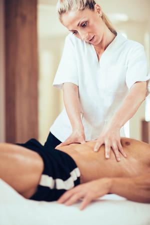 massage homme: therapyst physique massage sportif estomac Banque d'images