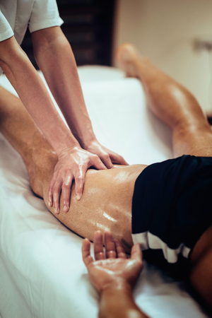 hands massage: Female physical therapyst massaging leg of male athelete Stock Photo