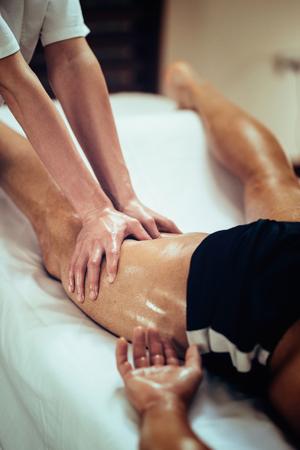 massieren: Weibliche k�rperliche therapyst Massieren Bein des m�nnlichen athelete