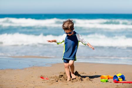 demolishing: Little boy demolishing sand castle on the beach