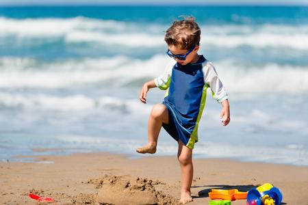 demolishing: Cute boy demolishing sand castle on the beach Stock Photo