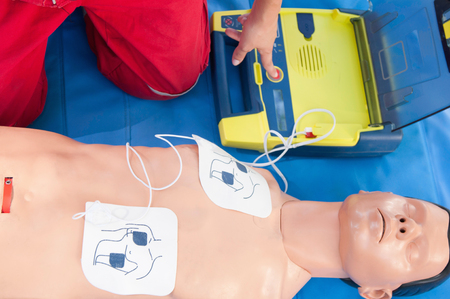 activating: Paramedic activating portable defibrillator connected to CPR dummy during resuscitation training. Focus on CPR dummy