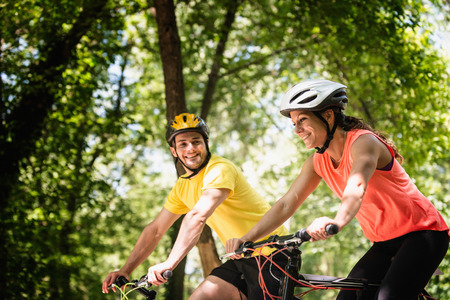 adults only: Young smiling couple riding bicycles