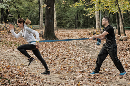 outdoor training: Female sprinter in hard training with resistance band Stock Photo