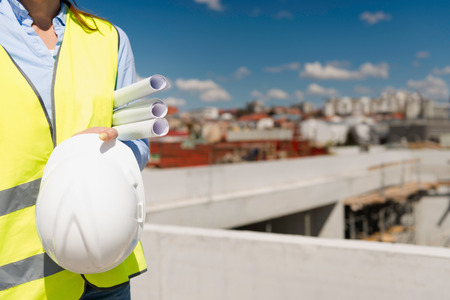 Architect with plans and hardhat on a construction site