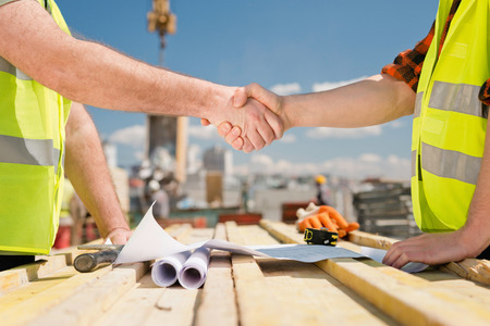 Hanshake seals an agreement at construction site Stock Photo