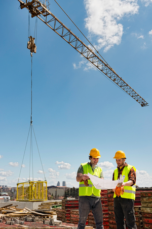 tower crane: Construction workers looking at building plans under the tower crane