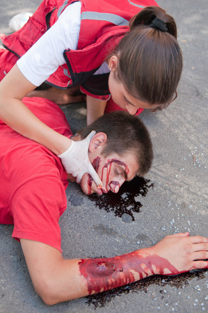 paramedic: Paramedic performs triple catch medical manouver to enable breathing of an unconcious  car accident victim