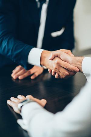 Business people reaching agreement, shaking hands. Toned image, focus on handsake 版權商用圖片