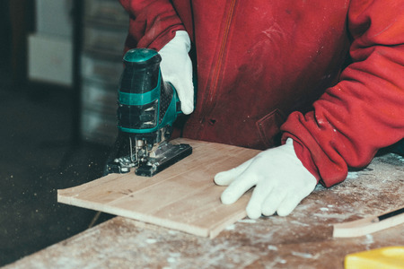 cutting through: Carpenter cutting through wooden plank with power saw Stock Photo