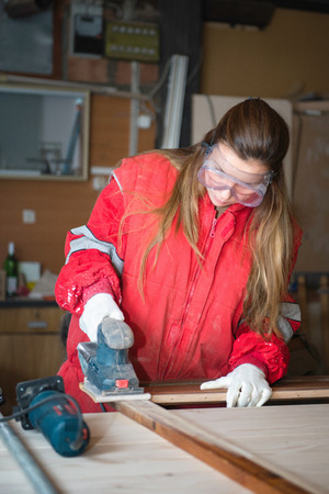 power tool: Female manual worker using power tool Stock Photo