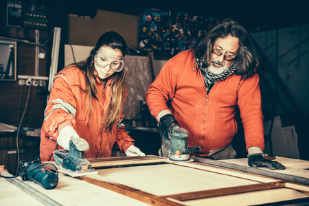Small family business - Father doing carpentry work with his daughter Stock Photo
