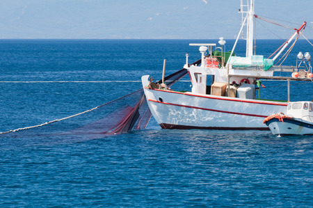 trawler net: Mediterranean fishing boat puliling nets out. Polarizing filter Stock Photo