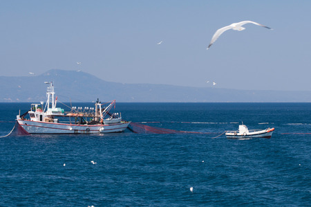 trawler net: Trawler and fishing boat spreading fishing net Stock Photo