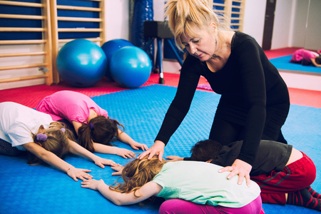 corrective: Corrective gymnastics - Physical therapist working with group of children, exercising spinal flexibility, improving body posture, positively influencing growth and development