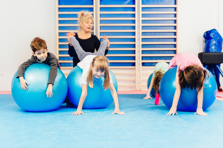 physical education: Group of children at physical education, exercising with fitness balls