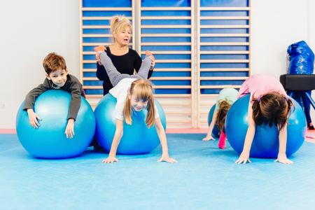 educacion fisica: Grupo de niños en la educación física, el ejercicio con pelotas para ejercicios