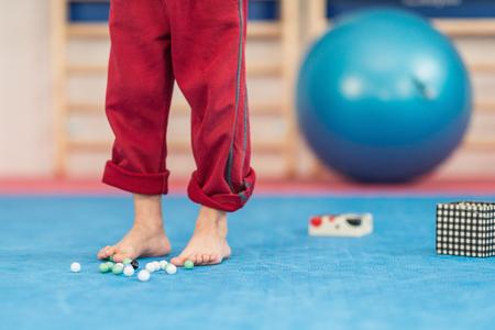 Les pieds plats de thérapie physique - Petit garçon ramasser des billes avec ses pieds, le développement des habiletés motrices des pieds et de la flexibilité