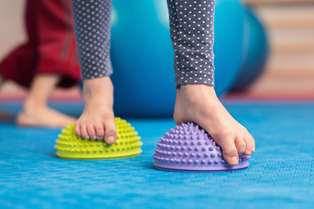 barefoot girls: Flat feet correction exercise - Girl walking over spiked half balance massage balls