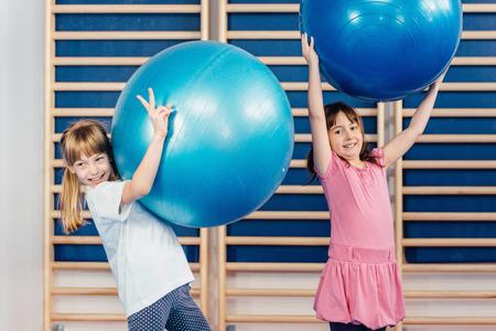 girls having fun: Two little girls having fun with fitness balls in school gymnasium Stock Photo