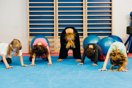 physical education: Group of little children at physical education class, exercising with teacher, doing simple posture improvement exercises Stock Photo