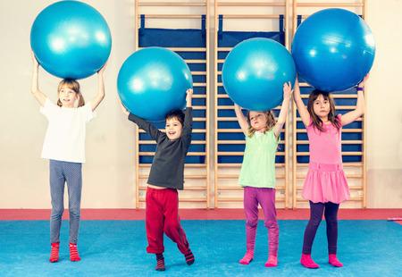 educacion fisica: Niños en la clase de educación física, jugando con bolas de la aptitud Foto de archivo