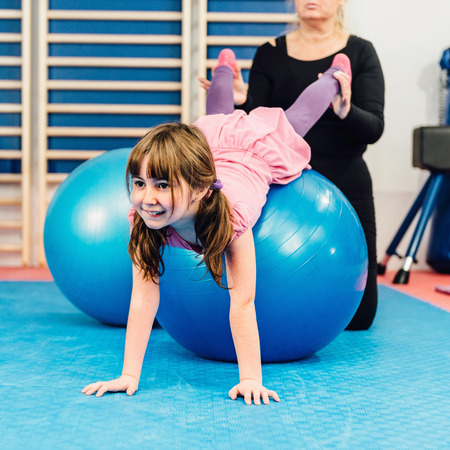 Physical therapist working with little girl in gym, exercising with fitness ball