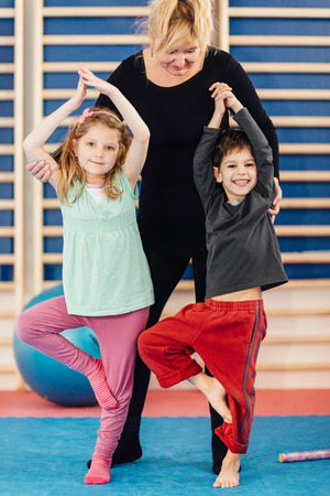 physical education: Group of little children with teacher on physical education class. Trying to stand on one leg, keeping balance Stock Photo