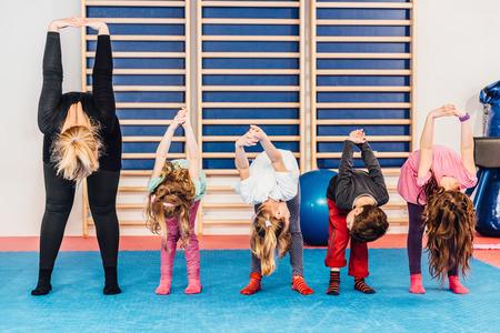 educacion fisica: Grupo de ni�os en la educaci�n f�sica, el ejercicio con el maestro