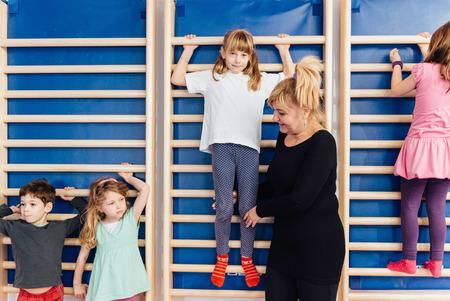 recreational climbing: Little children climbing wall bars in school gymnasium