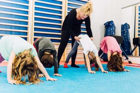 physical education: Group of children at physical education, exercising with teacher