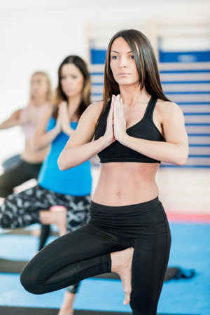 tree position: Women in tree pose on yoga class