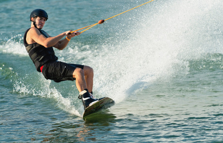 exhilaration: Young man on wakeboard, creating large wall of water