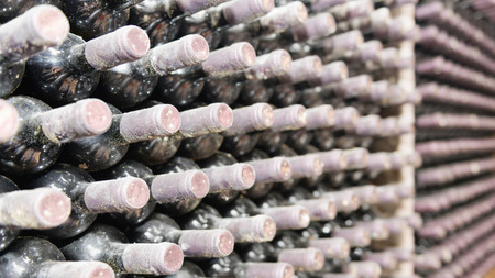 rack arrangement: Detail from huge wine cellar. Racks with thousands of wine bottles covered in dust. Selective focus set on bottles close to camera Stock Photo