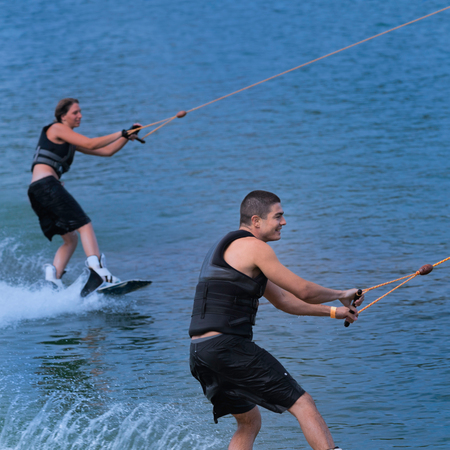 two person only: Young couple wakeboarding together, having fun