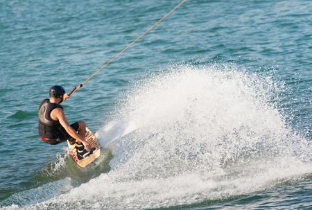 waterskiing: Young sportsman wakeboarding on lake Stock Photo