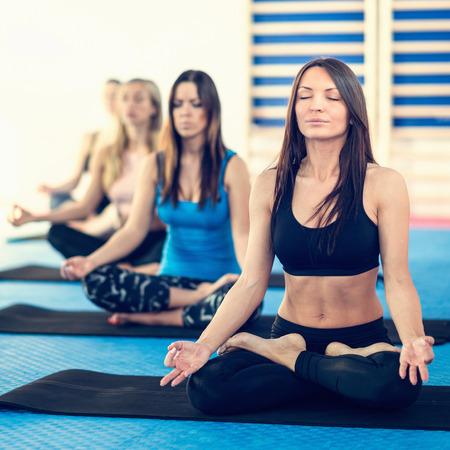 good posture: Grupo de mujeres que practican yoga en el centro de bienestar