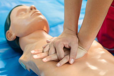 chest compression: Woman giving chest compression to CPR doll