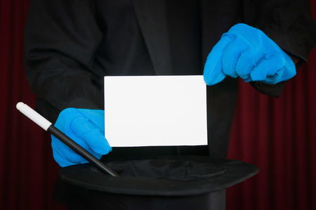 stage performer: Stage performer with blue gloves presents a blank card