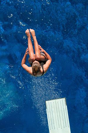 springboard: Mujer buceador trampolín cogido en el aire durante la inmersión voltereta hacia atrás.