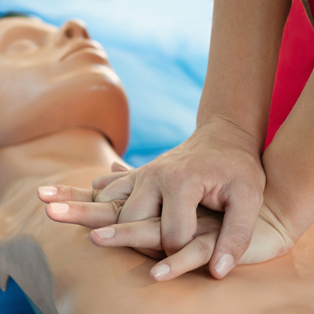 compression: Chest compression demonstration on CPR doll by woman