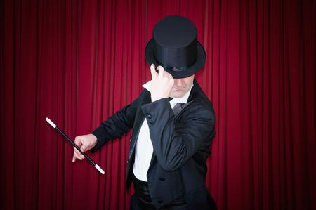 cortinas rojas: Mago que se realiza en el escenario con cortinas rojas Foto de archivo