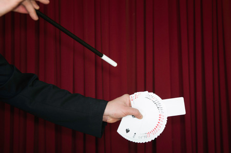 pull out: Magician usesd wand to pull out blank card from deck Stock Photo