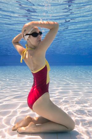 Onderwater jonge vrouwelijke gesynchroniseerd zwemmer Stockfoto